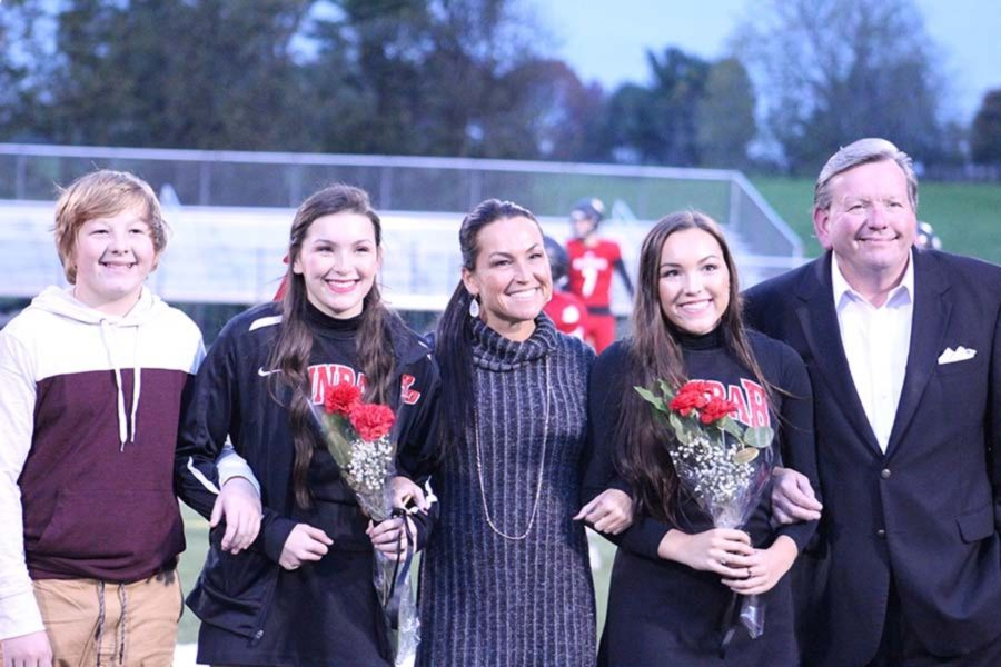 Senior cheerleaders Mallory and Macy Baker pose with their parents and younger brother.
