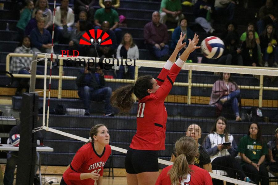 #11 Senior Savannah Dudek hits the ball over the net.