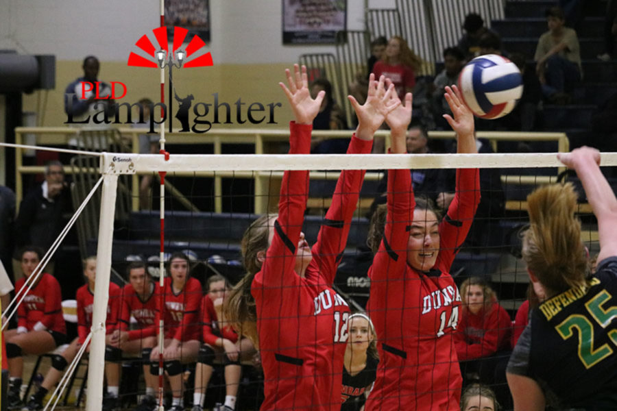 #12 Junior Meredith Phillips and #14 Sophomore Eleanor Davis both jump high to block the ball.