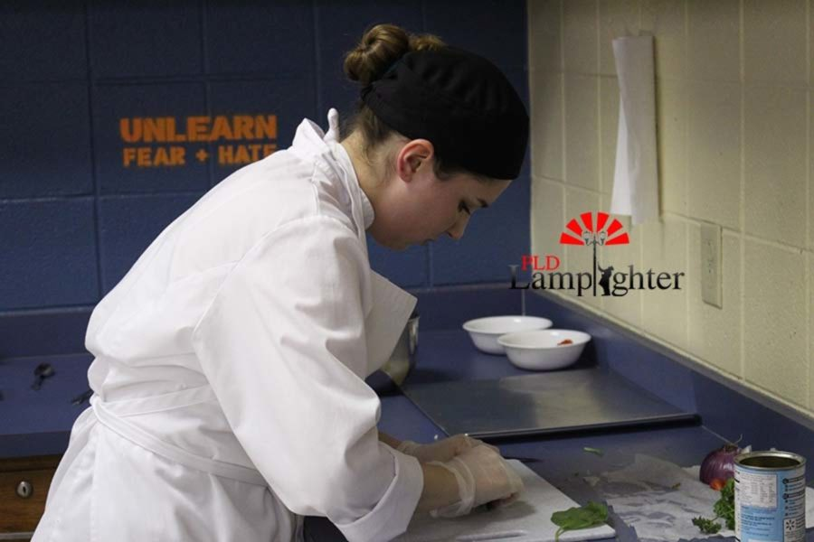 Senior Sarah Morrison preparing to move the chopped vegetables into the pot to cook during the Top Chef competition. Sarah was on the winning team.