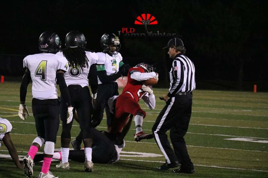 A Dunbar player gets tackled by the feet at the end of the play.