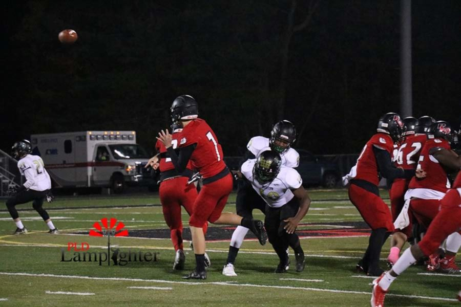 #7 Junior Tanner Cox throwing a pass before getting tackled.