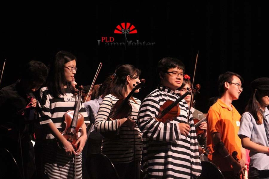 The Symphony Orchestra first violins, dressed as prisoners, take a bow after finishing their pieces.