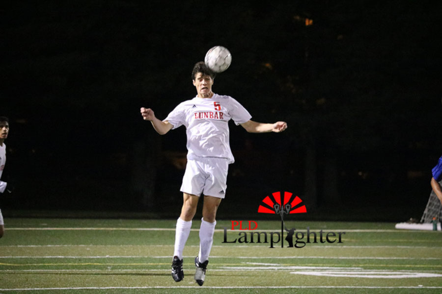 #5 Senior Jackson Akins headbutts the ball.