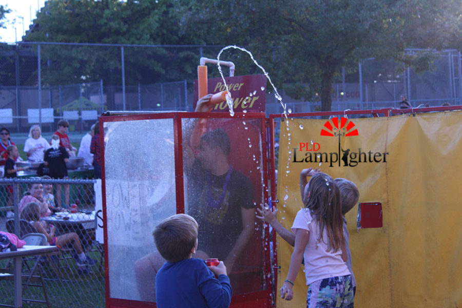 English teacher Mr. Michael Mau sprays his children from the dunk booth.