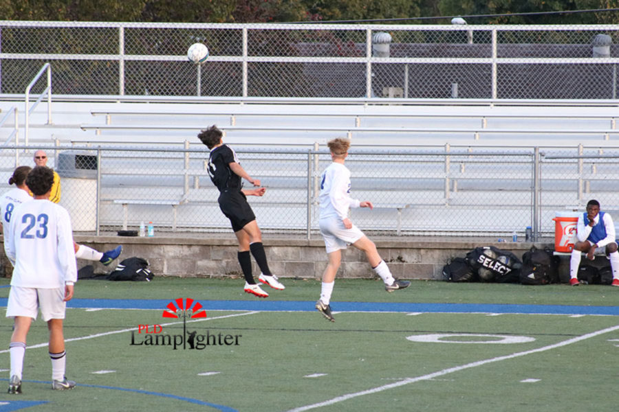 #11 Sullivan Curd heading the ball away from a defender.