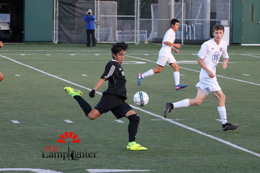 #19 Pedro Jiminez volleying the ball towards the goal.