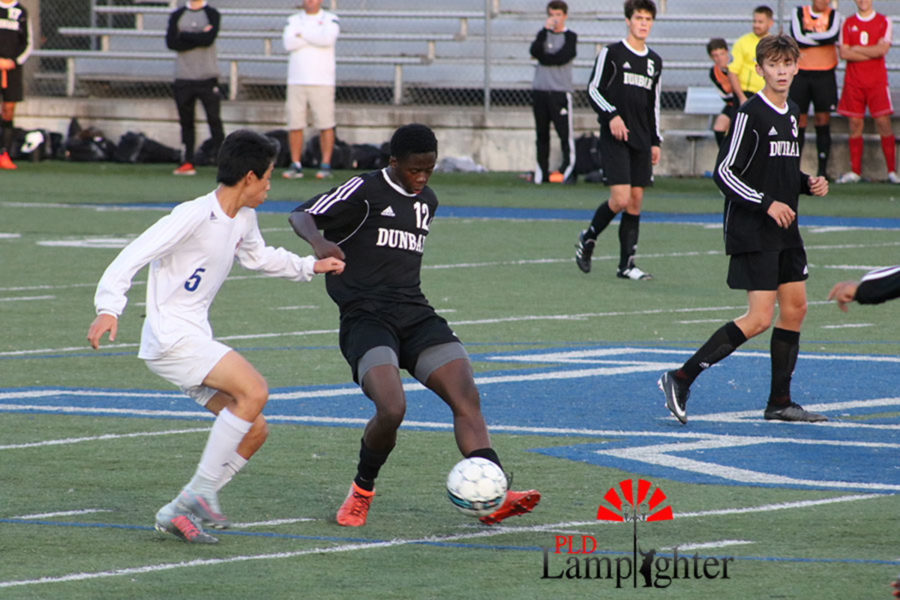 #12 Junior Andrew Pascal using ball skills to avoid a defender.