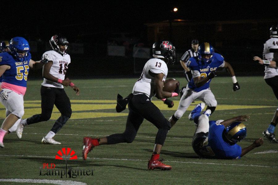 #13 Freshman Dre Thruston runs the ball trying to get down field.