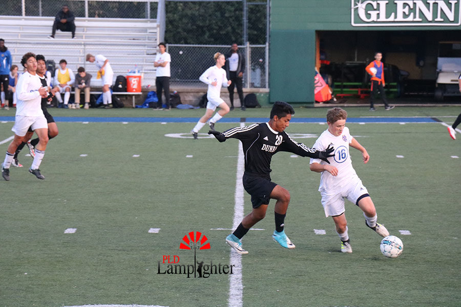 #20 Sophomore Isaac Delgado tries to steal the ball from an opposing player.
