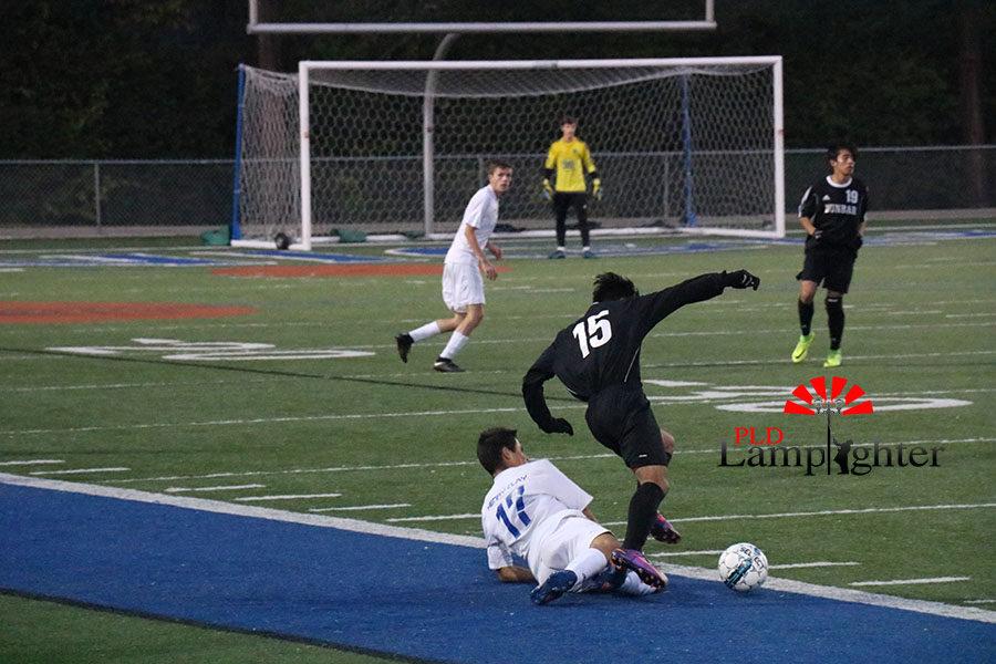 #15 Sophomore Crescenio Torres kicks the ball past a fallen player.