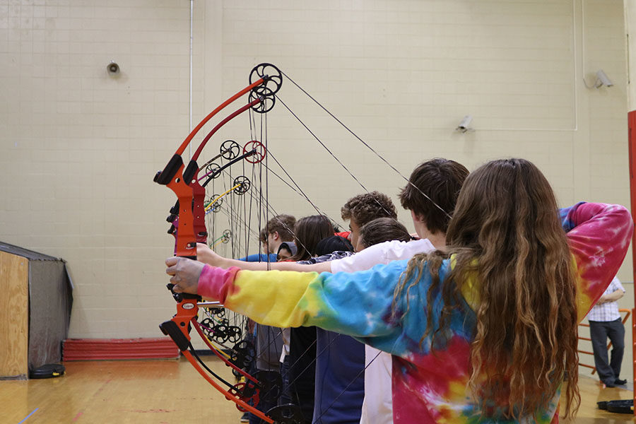 The Archery team lines up to stretch with their bows.