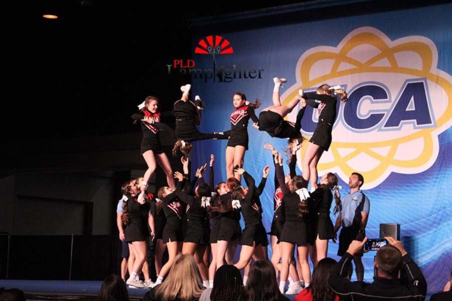 Dunbar cheerleaders flipping during the pyramid stunt.