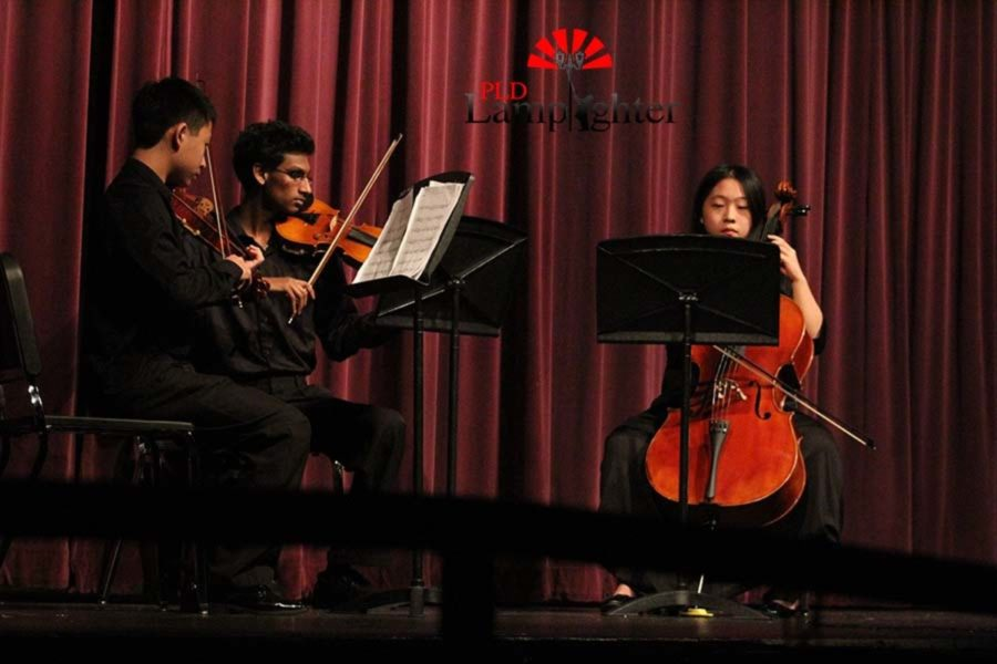Helen Pang playing the cello accompanied by violinists.