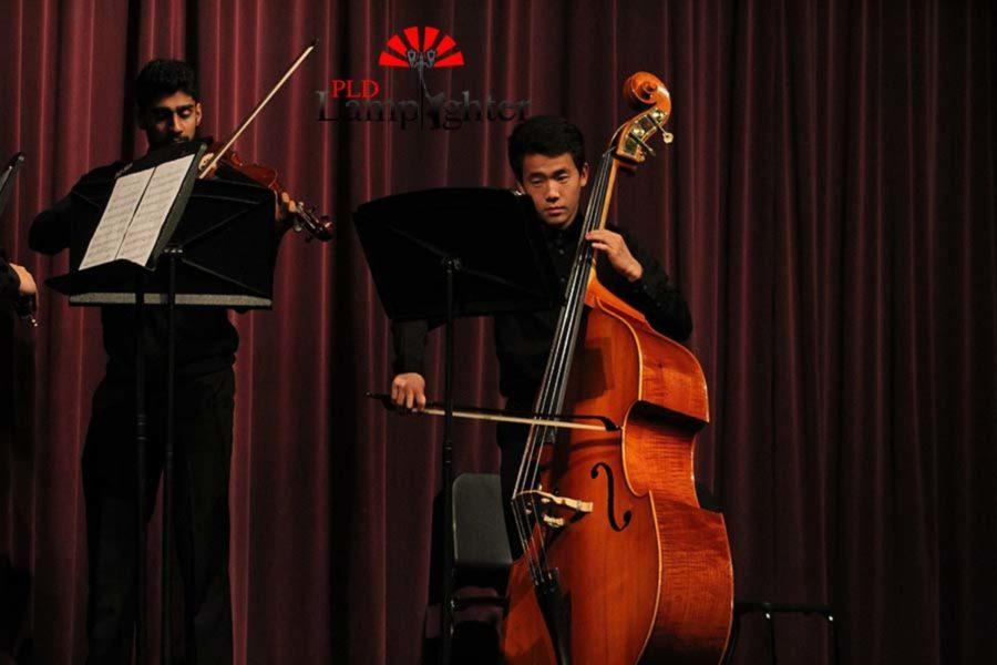 Sai Naidu playing violin and Kevin Jing playing bass.