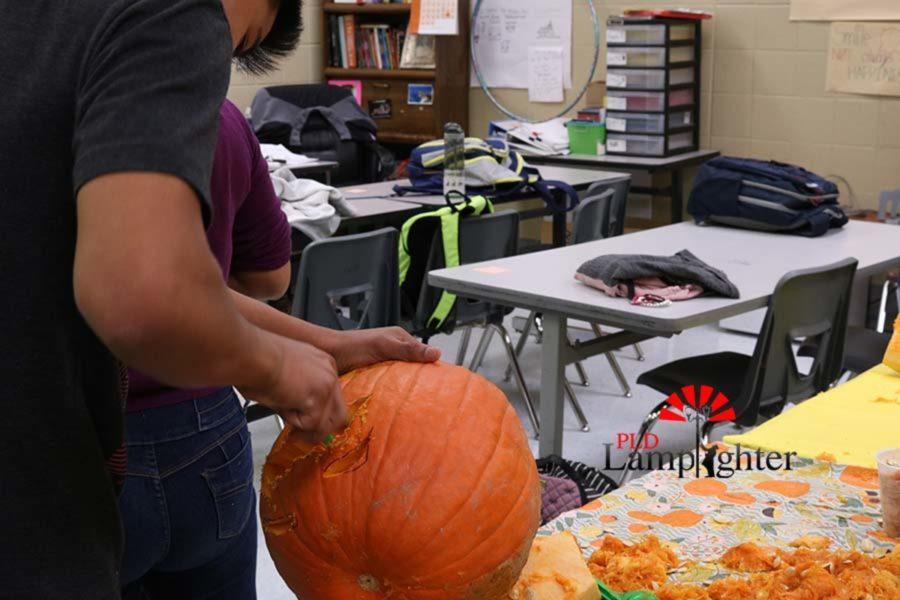 An ESL student prepares a jack-o-lantern.