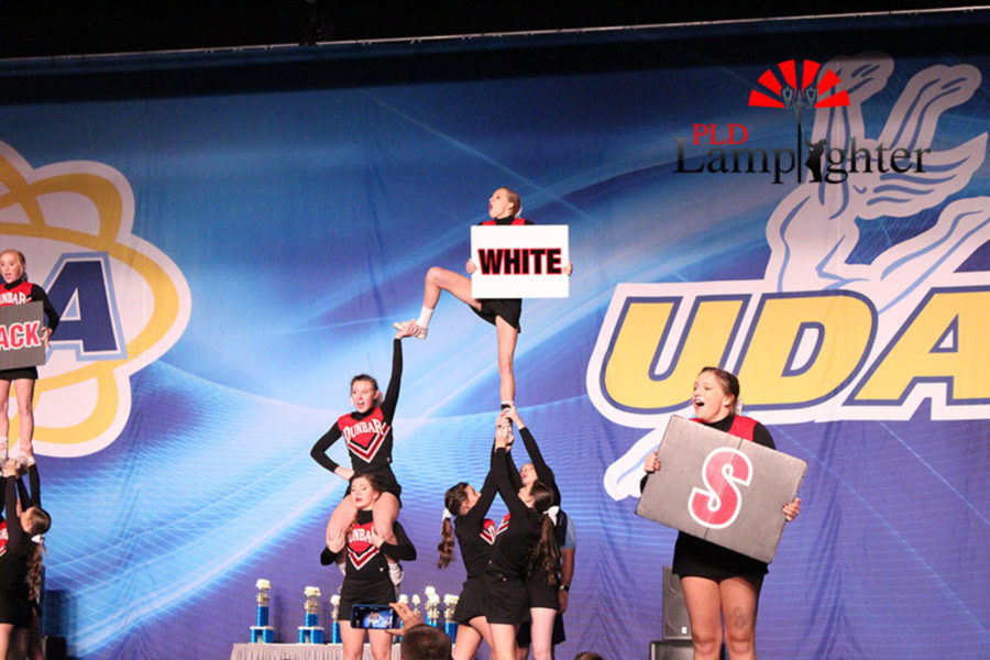 Marissa Rajcan leading the cheerleaders in a stunt.