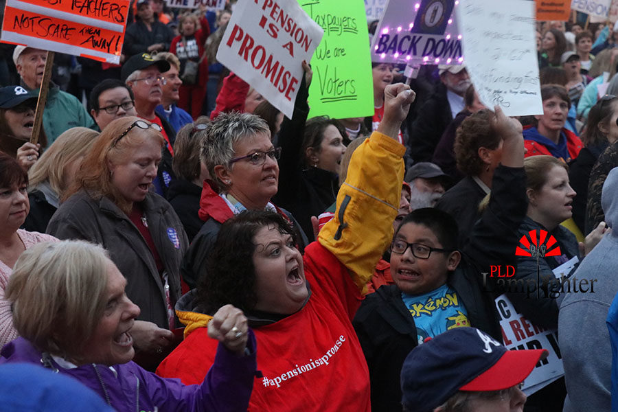 A group of teachers yell in support of the fight for pensions.