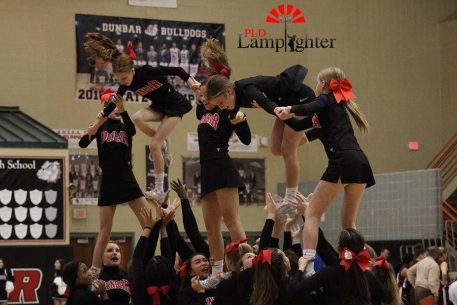 Red team cheerleaders performing their pyramid stunt.