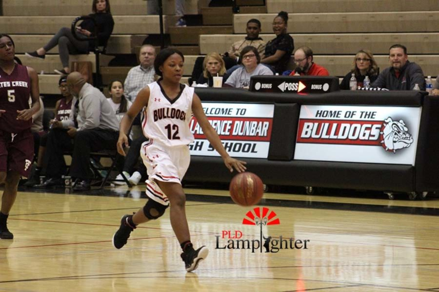 #12 DelTarria Jackson dribbles the ball down the court.