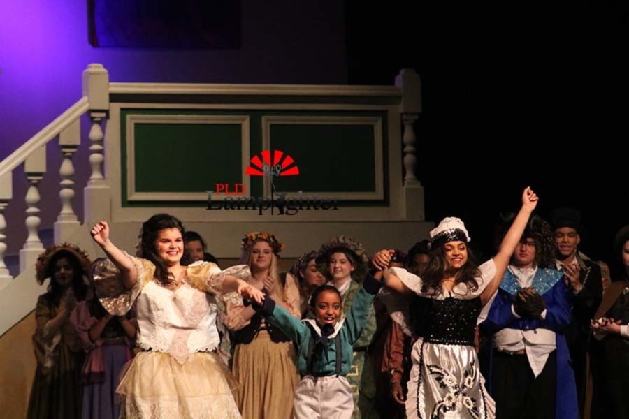 Rachael Prewitt, Hadley Roach, and Maya Anjur raise their arms as the audience claps for them.