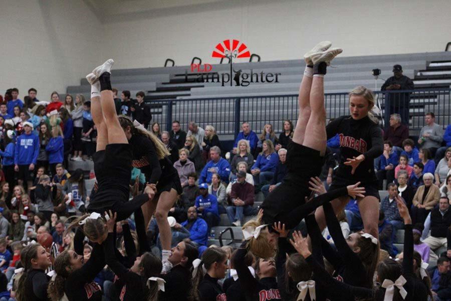 Cheerleaders perform an inversion stunt.