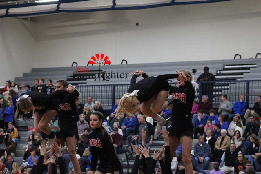 Junior Natalie Rowe and Senior Julia Beard tuck for a front flip in the pyramid.