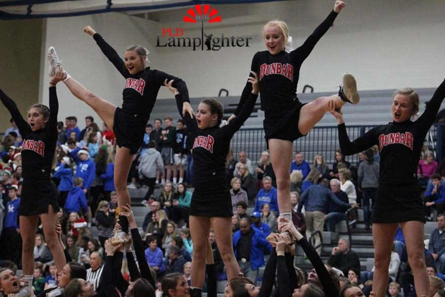 The cheerleaders hit their motions to finish off the pyramid.