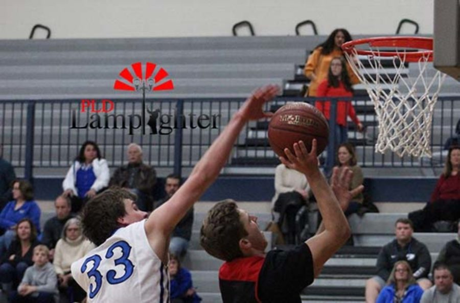 #12 Jared Gadd shoots the layup as the defender attempts to block it.