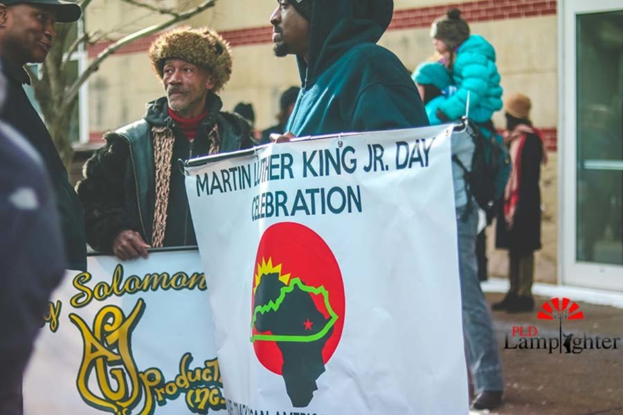 March participants converse at the end of the event. Individuals bundled up in the cold weather to commemorate MLK. The march served a place for many different community members to communicate as the men held two different banners.