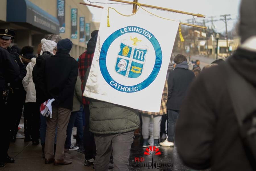 Students from Lexington Catholic high school march in MLK walk. Lexington Catholic's banner included several symbols of the Christian belief. Lexington Catholic students bundled up to withstand the cold weather and participate in the walk.