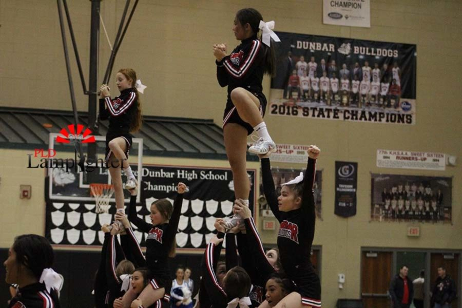 Red team cheerleaders perform a stunt for the crowd.