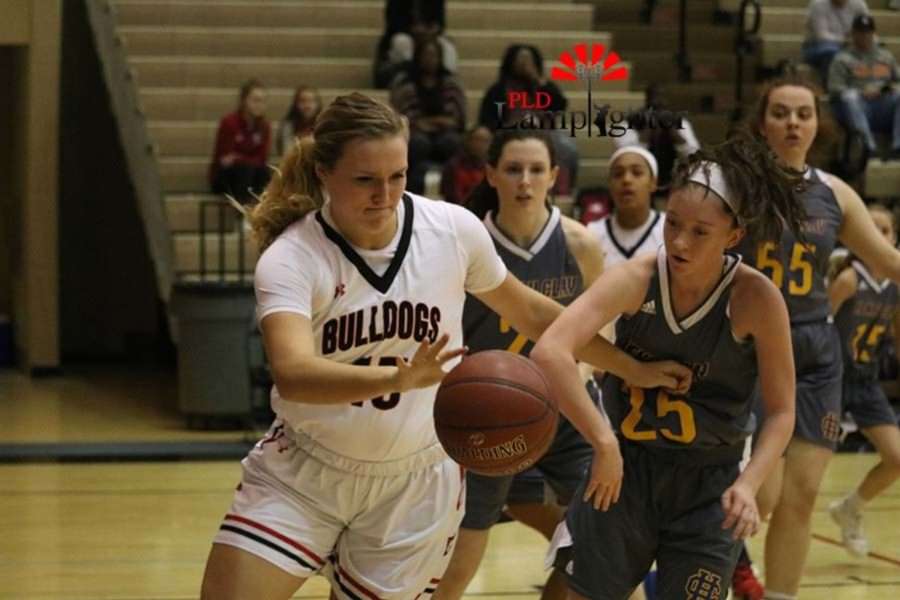 #45 Senior Brooke Hill dribbles the basketball around an opposing player.
