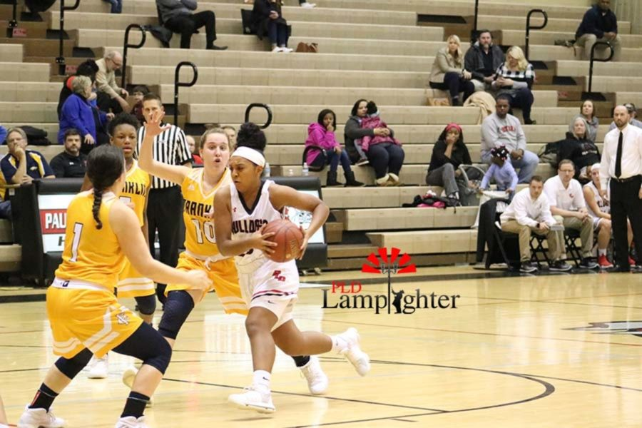 #23 Mashayla Cecil drives the ball into the paint with two defenders trying to stop her.
