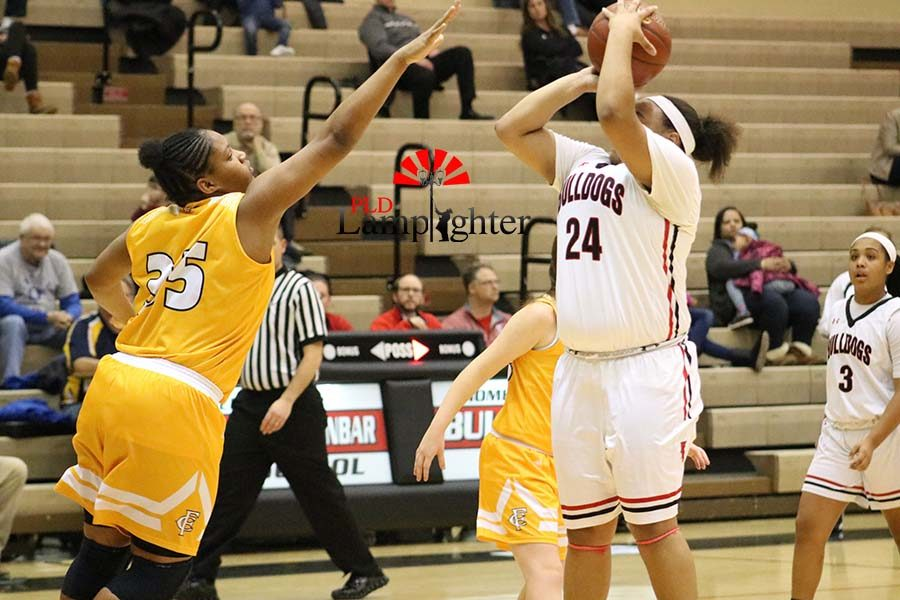 #24 Senior Anaiyah Cotton shooting with the defender putting a hand in her face