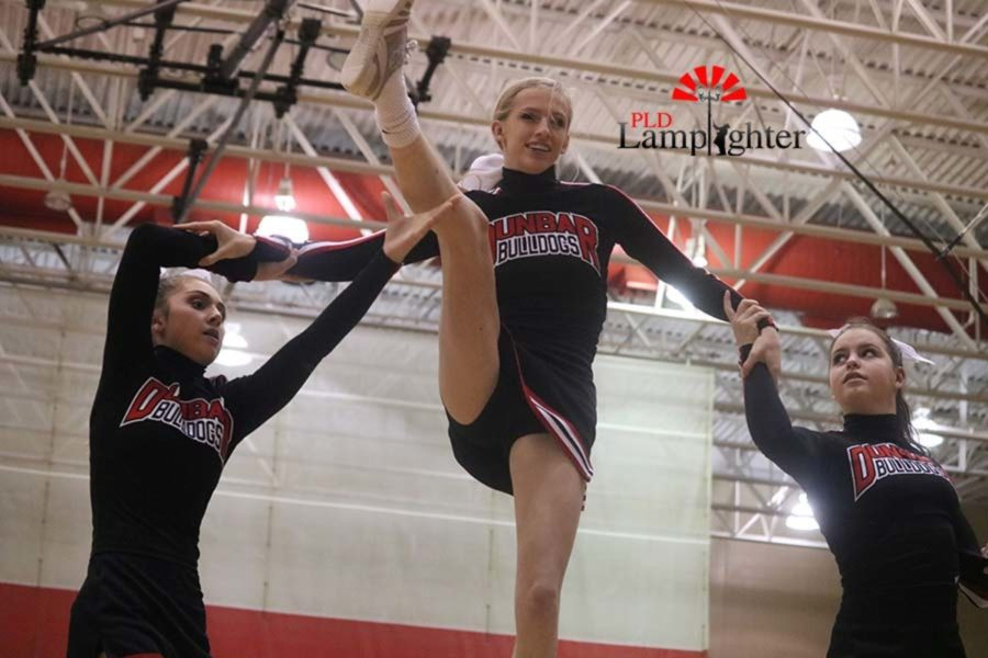 Sophomore cheerleader Marissa Rajcan is supported by her teammates during a pyramid stunt.