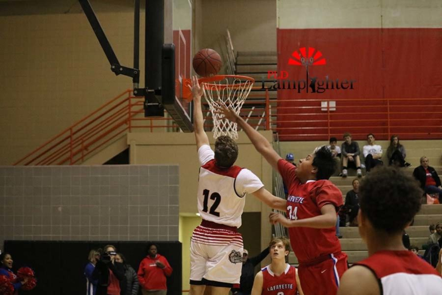 #12 Junior Jared Gadd shoots the layup with a defender closing in to contest the shot.