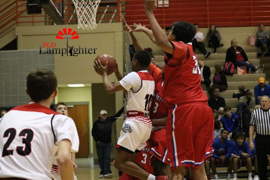 #10 Senior JaQuice Gray shoots the layup with two defenders attempting to block the shot.