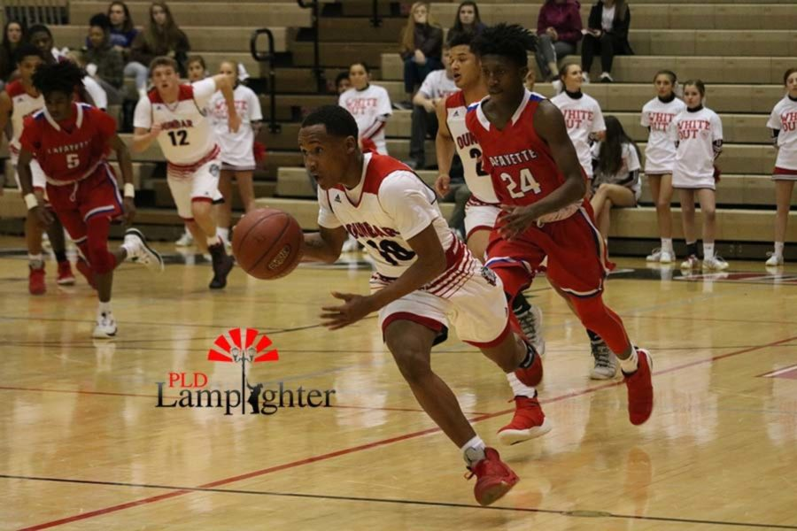 #10 Senior JaQuice Gray pushes the ball up court looking to make a play.