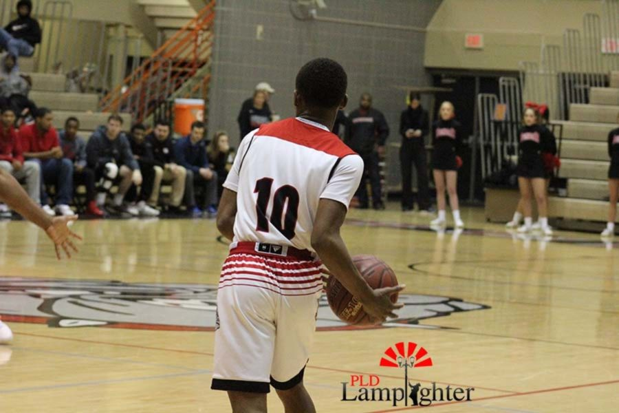 #10 Senior JaQuice Gray dribbling down the court.