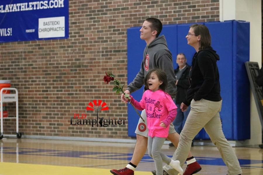 Senior Alex Spaulding escorted out by his mom and sister at Senior Night.