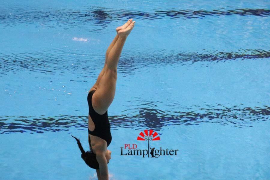 Freshman Alexis Radhakrishnan enters the water to complete her dive.