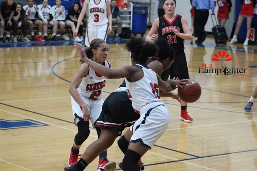 #23 Senior Mashayla Cecil  dribbles through two defenders.