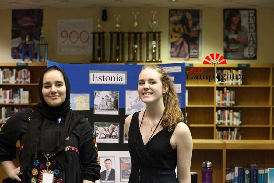 Seniors Sunny Ghuneim and Anna Susini pose with their group's board of Estonia.