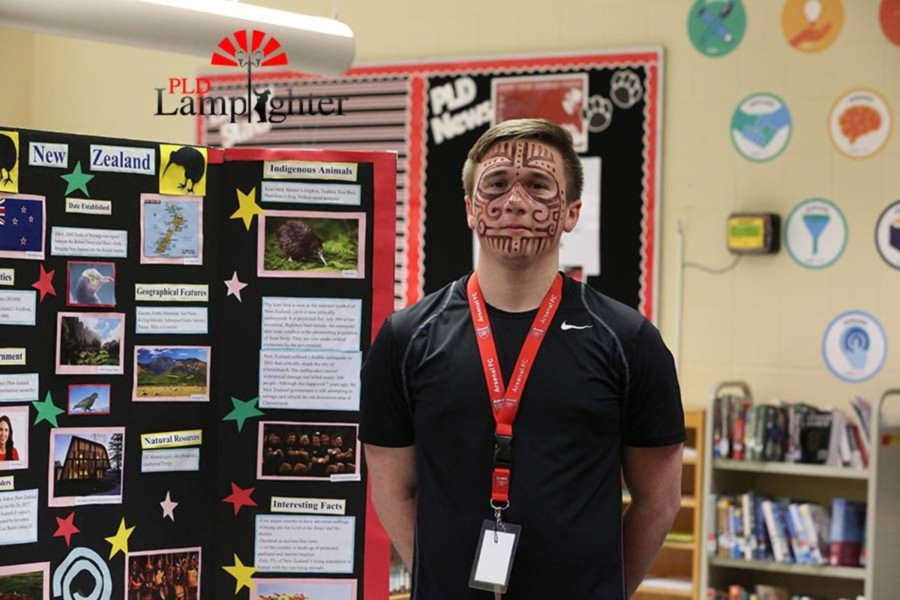 Senior Chris Duncan wears face paint as he poses next the country of New Zealand poster.