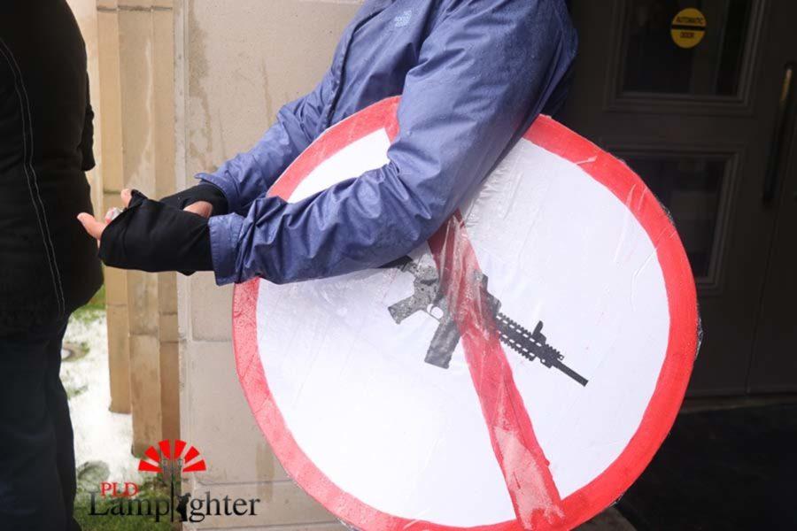 An attendee holds an anti-gun poster.