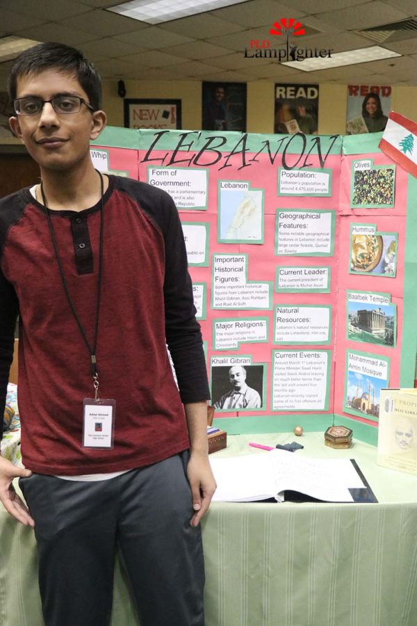 Sophomore Adeel Ahmed poses with his team's poster of Lebanon.