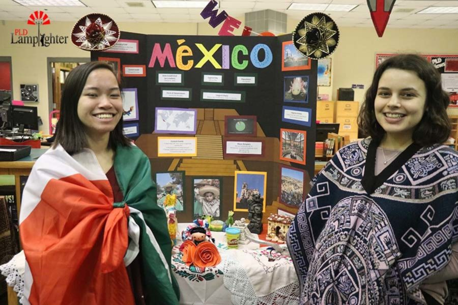 Junior Savannah Fisher and  Senior Kristen Silvestri dress in traditional Mexican clothing to present their booth.