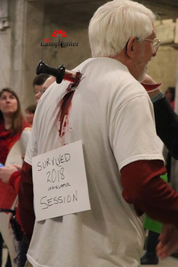 A man has a fake knife through his back and wears a sign stating,