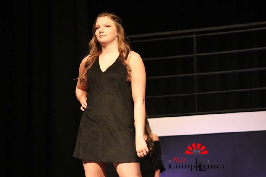 Junior Jenna Helmburg posing in a black suede dress.